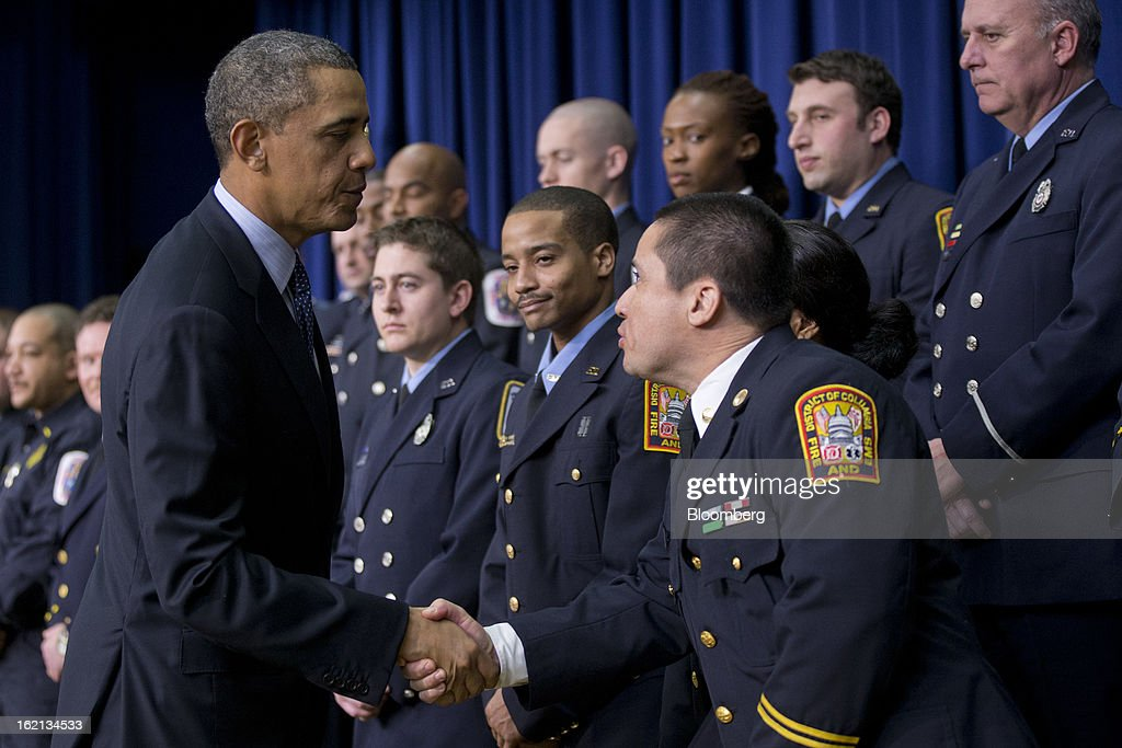 U.S. President <a gi-track='captionPersonalityLinkClicked' href=/galleries/search?phrase=Barack+Obama&family=editorial&specificpeople=203260 ng-click='$event.stopPropagation()'>Barack Obama</a>, left, shakes hands with emergency responders after speaking in the South Court Auditorium of the Eisenhower Executive Building next to the White House in Washington, D.C., U.S., on Tuesday, Feb. 19, 2013. Obama stepped up pressure on Congress to avert 'brutal' automatic $1.2 trillion in budget cuts set to kick in March 1, saying it would harm the economy and curtail vital services. Photographer: Andrew Harrer/Bloomberg via Getty Images