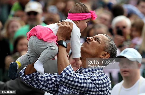 S President Barack Obama lifts Stella Munoz into the air while greeting guests on the South Lawn of the White House during the annual White House...