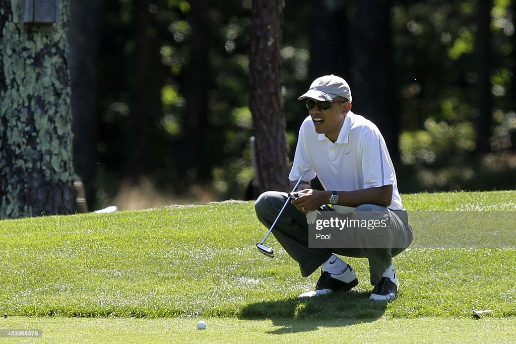 President Barack Obama lines up a putt on the first green at the Farm Neck Golf Club on August 9 2014 in Oak Bluffs Massachusetts The Obama's are...