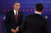 S President Barack Obama listens as Republican presidential candidate Mitt Romney speaks during a town hall style debate at Hofstra University...