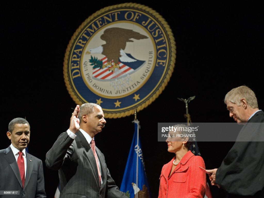 US President Barack Obama(L) listens as US Attorney General Eric H. Holder Jr. is sworn-in, with his wife, Dr. Sharon Malone holding the Bible, as Judge Robert I. Richter (R) conducts the installation ceremony of Holder as the 82nd Attorney General of the United States on March 27, 2009 at the George Washington University Lisner Auditorium in Washington, DC. AFP Photo/Paul J. Richards