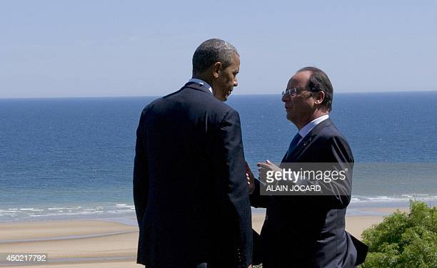 US President Barack Obama listens to French President Francois Hollande over Omaha Beach during a joint FrenchUS DDay commemoration ceremony at the...