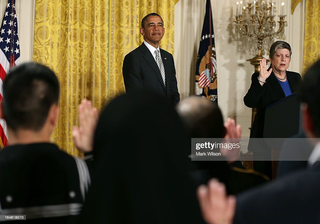 U.S. President Barack Obama listens to Homeland Security Secretary Janet Napolitano administer the oath of allegiance during a naturalization ceremony in the East Room of the White House on March 25, 2013 in Washington DC. Napolitano administered the oath of allegiance to active duty service members and civilians officially granting them United States citizenship.