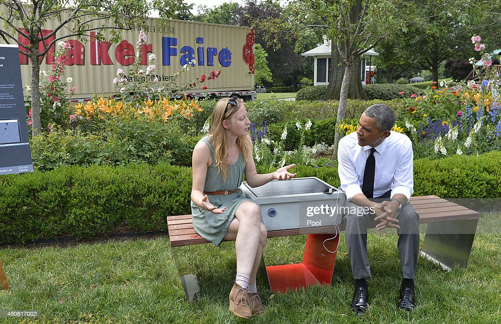 U.S. President <a gi-track='captionPersonalityLinkClicked' href=/galleries/search?phrase=Barack+Obama&family=editorial&specificpeople=203260 ng-click='$event.stopPropagation()'>Barack Obama</a> (R) listens to Sandra Richter of Cambridge, Massachusetts, as they sit on an example of eco-friendly urban furniture, a solar-powered sofa, or 'soofa', which can be used to charge electronic items, at the White House Maker Faire in the Rose Garden, June 18, 2014 in Washington, DC. The Faire is a series of projects by students, entrepreneurs and regular citizens using new technologies and tools to launch new businesses and learning new skills in science, technology, engineering and mathematics.