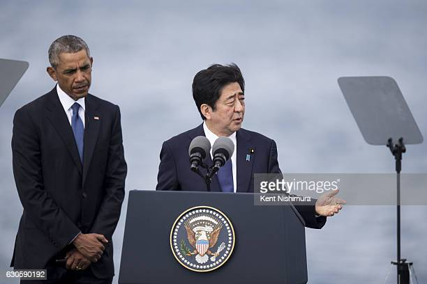 S President Barack Obama listens while Japanese Prime Minister Shinzo Abe delivers remarks at Joint Base Pearl Harbor Hickam's Kilo Pier on December...