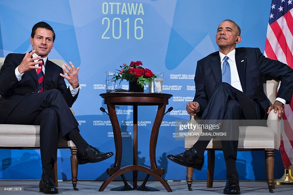 US President Barack Obama (R) listens while Mexican President Enrique Pena Nieto makes a statement to the press after a meeting during the North American Leaders Summit at the National Gallery of Canada on June 29, 2016 in Ottawa, Ontario. / AFP / Brendan Smialowski