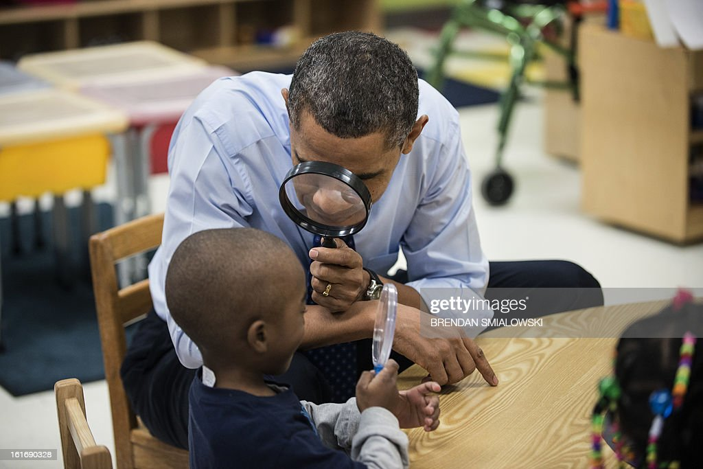 US President Barack Obama looks at a boy with a magnifying glass while visiting children at College Heights Early Childhood Learning Center February 14, 2012 in Decatur, Georgia. Obama is traveling to Georgia to promote economic and educational initiatives he spoke about in this week's State of the Union. AFP PHOTO/Brendan SMIALOWSKI