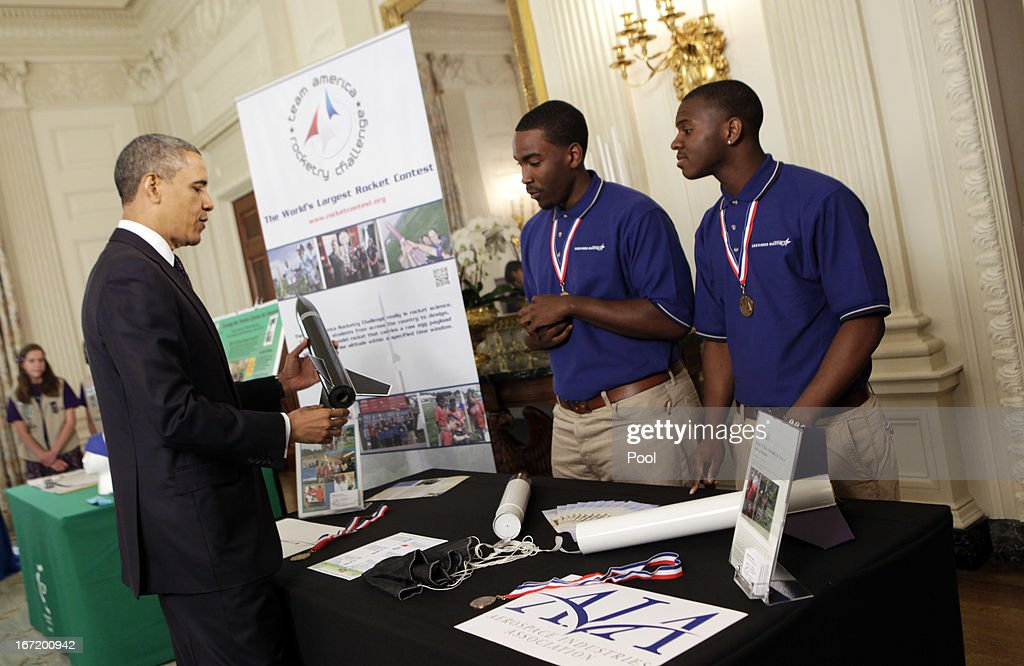 U.S. President Barack Obama looks at a rocket created by Wooddale High School's students Wesley Carter and Darius Hooker from Memphis, Tennessee in the State Dining Room of the White House at the White House Science Fair April 22, 2013 in Washington, DC. The White House Science Fair celebrates the student winners of a broad range of science, technology, engineering and math (STEM) competitions from across the country. The first White House Science Fair was held in late 2010.