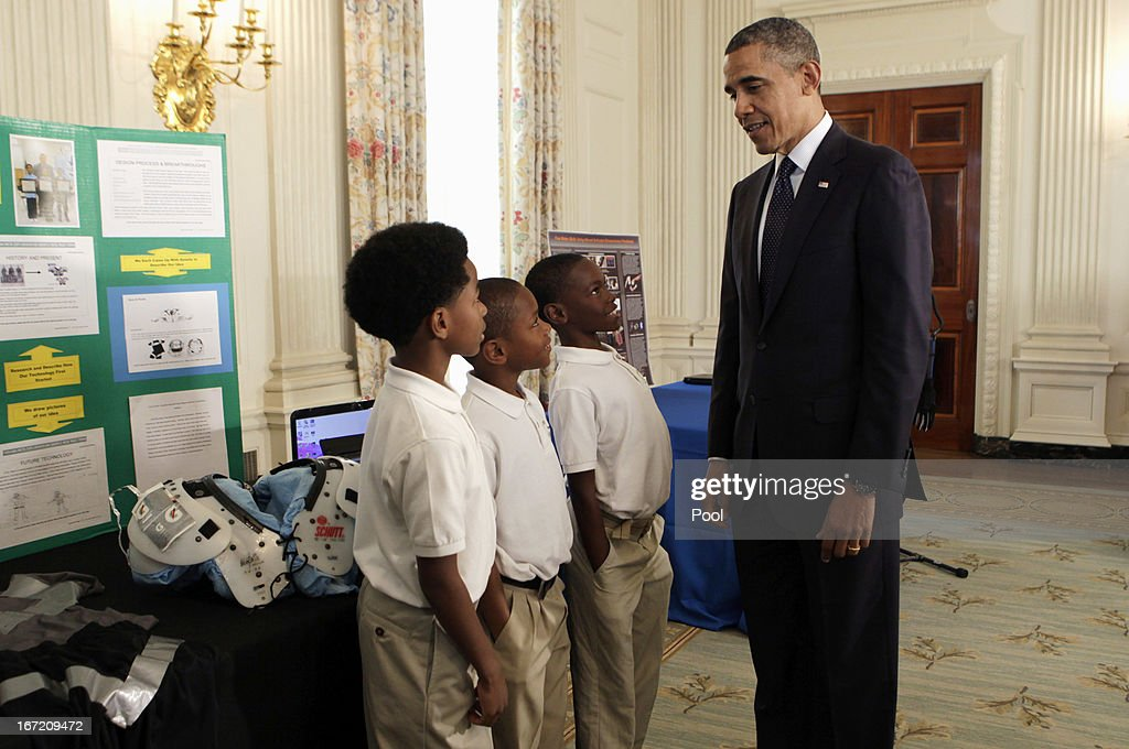U.S. President Barack Obama looks at the COOL PADS for shoulders, helmet, armpits and groin created by Evan Jackson, Alec Jackson and Caleb Robinson, from Flippen Elementary School students from McDonough, Georgia, in the State Dining Room of the White House during the White House Science Fair April 22, 2013 in Washington, DC. The White House Science Fair celebrates the student winners of a broad range of science, technology, engineering and math (STEM) competitions from across the country. The first White House Science Fair was held in late 2010.