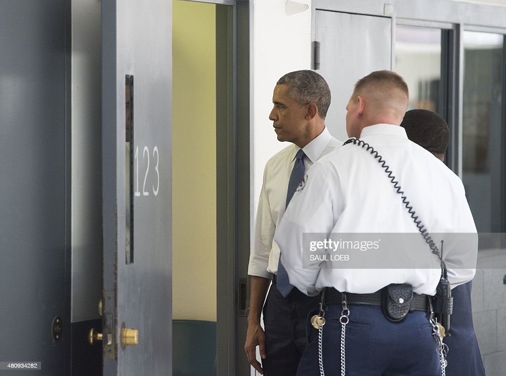 US President Barack Obama looks into a prison cell alongside Ronald Warlick a correctional officer as he tours a cell block at the El Reno Federal...