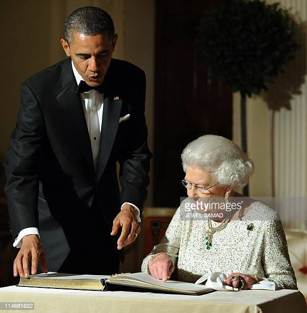 US President Barack Obama looks on as Britain's Queen Elizabeth II signs a guest book after a reciprocal dinner at the Winfield House in London on...