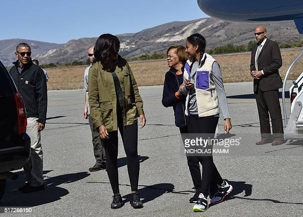 US President Barack Obama looks on as First Lady Michelle Obama says goodbye to her mother Marian Robinson and daughter Sasha as they go their...