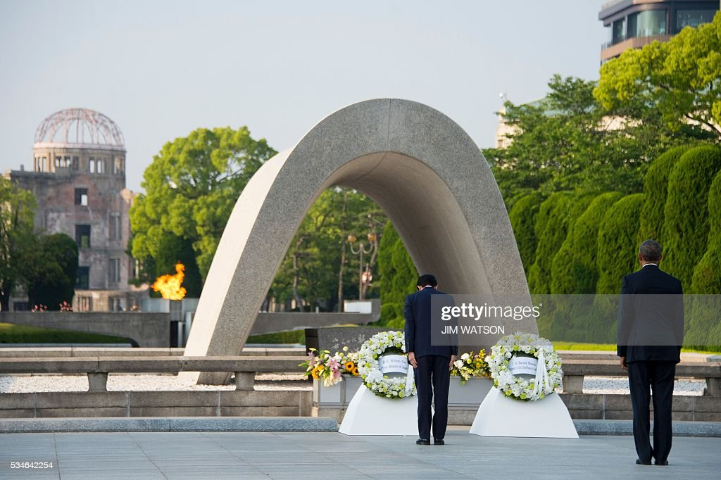 US President Barack Obama (R) looks on as Japanese Prime Minister Shinzo Abe (C) lays a wreath during a visit to the Hiroshima Peace Memorial Park in Hiroshima on May 27, 2016. Obama on May 27 paid moving tribute to victims of the world's first nuclear attack. WATSON