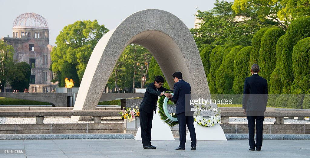 US President Barack Obama (R) looks on as Japanese Prime Minister Shinzo Abe (C) prepares to lay a wreath during a visit to the Hiroshima Peace Memorial Park in Hiroshima on May 27, 2016. Obama on May 27 paid moving tribute to victims of the world's first nuclear attack. WATSON