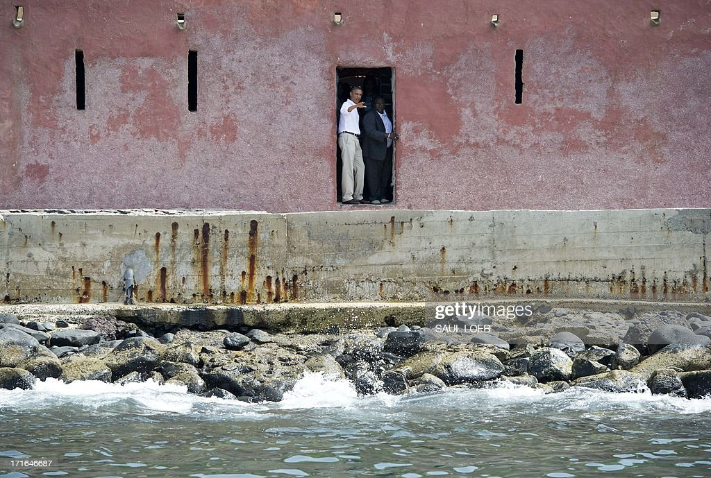 US President Barack Obama (L) looks out from the Door of No Return alongside his guide, Eloi Coly (R), during a visit to the House of Slaves, or Maison des Esclaves, at Goree Island off the coast of Dakar on June 27, 2013. Obama and his family toured the museum at the site where African slaves were held before going through the door and being shipped off the continent as slaves.