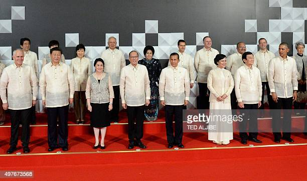 US President Barack Obama looks over at host Philippine President Benigno Aquino and China's President Xi Jinping as they are joined by leaders and...