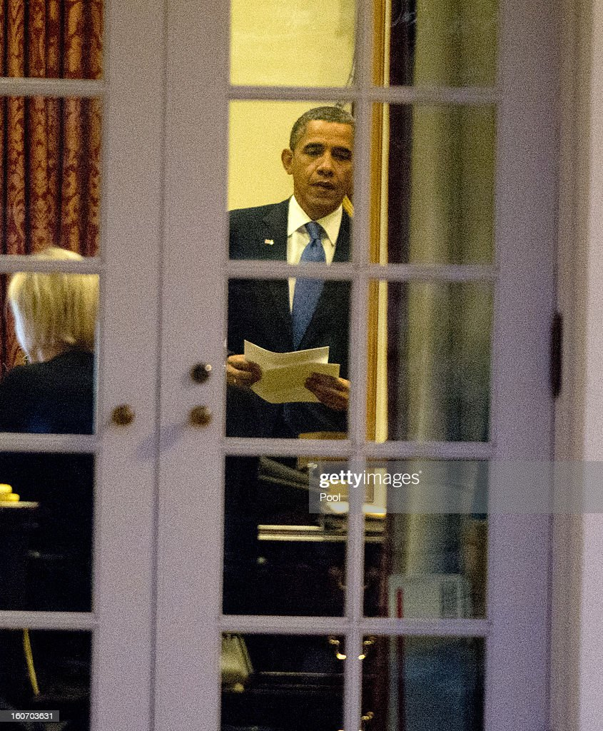 U.S. President Barack Obama looks over some papers in a West Wing office after arriving on the South Lawn of the White House on February 4, 2013 in Washington, D.C. Obama returned from a trip to Minneapolis, Minnesota to promote his initiative to reduce gun violence.