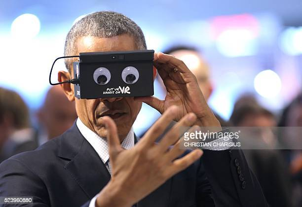 US President Barack Obama looks through a device next to the German Chancellor at the booth of German automation company ifm electronic as they tour...