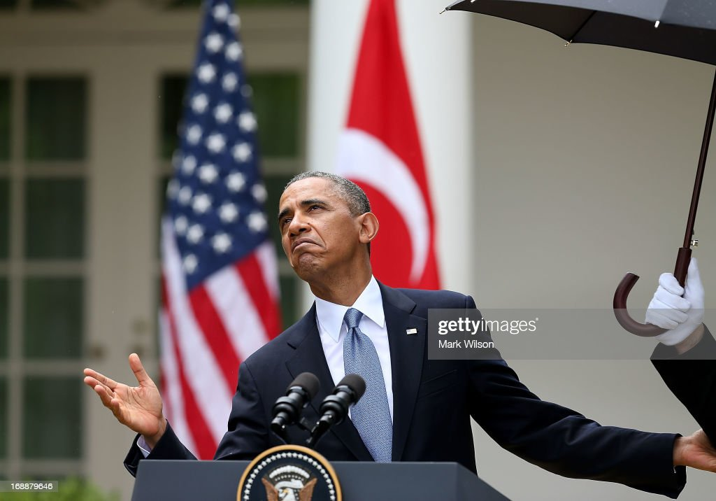 U.S. President <a gi-track='captionPersonalityLinkClicked' href=/galleries/search?phrase=Barack+Obama&family=editorial&specificpeople=203260 ng-click='$event.stopPropagation()'>Barack Obama</a> looks to see if it stopped raining as a U.S. Marine holds an umbrella for hims, during a news conference with Prime Minister Recep Tayyip Erdogan of Turkey (not shown), in the Rose Garden at the White House, May 16, 2013 in Washington, DC. President Obama answered questions on the IRS Justice Department invesigation.