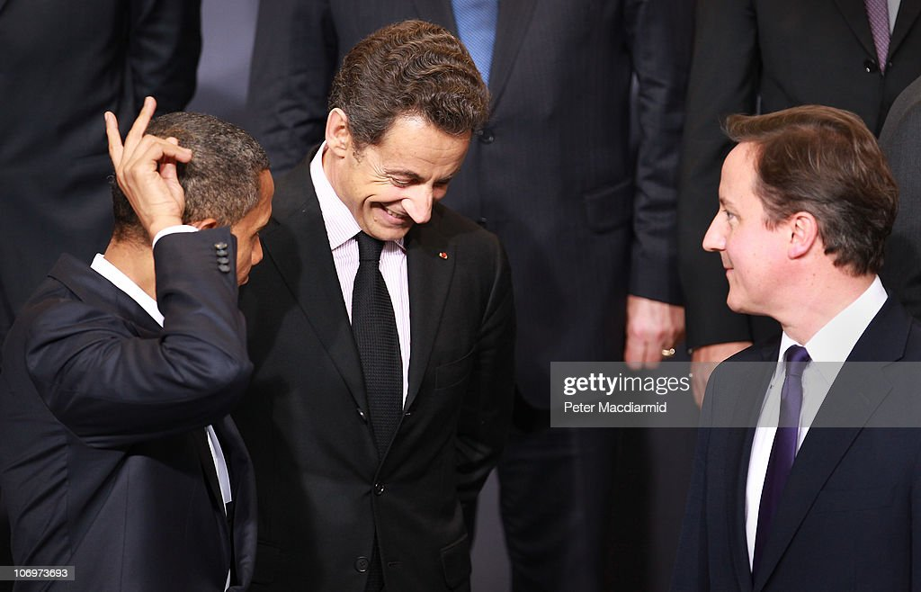President Barack Obama makes a 'rabbit ears' gesture as he stands with French President Nicolas Sarkozy and British Prime Minister David Cameron...
