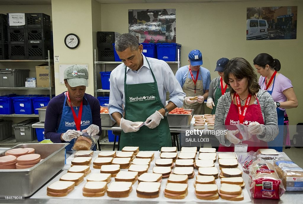 US President Barack Obama makes bologna sandwiches alongside volunteers Dolly Garcia (R), a federal employee from the US Census Bureau, and Chantelle Britton (L), a federal employee from the Department of Health and Human Services, at Martha's Table in Washington, DC, October 14, 2013, as the crisis over a US government shutdown and debt ceiling standoff continues into the third week of the shutdown. The non-profit organization helps low income and homeless families and many of the current volunteers are furloughed federal workers. AFP PHOTO / Saul LOEB