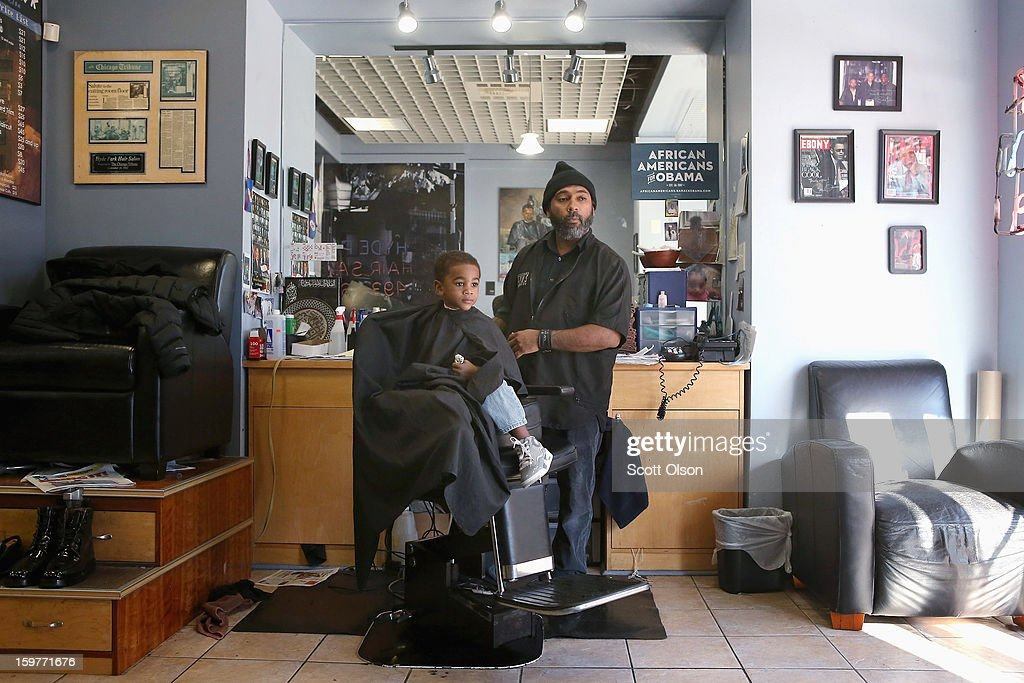 U.S. President Barack Obama memorabilia hangs on the walls at the Hyde Park Hair Salon behind barber Ishmael Coye as he looks for approval from three-year-old Bryson White's father after cutting the boy's hair shortly before Obama took the oath of office to officially start his second term on January 20, 2013 in Chicago, Illinois. Obama would get his hair cut at The Hyde Park Hair Salon, which is near his Chicago home, before he was elected to the White House. Chief Justice John Roberts administered the official swearing-in today and a public ceremony will take place January 21.