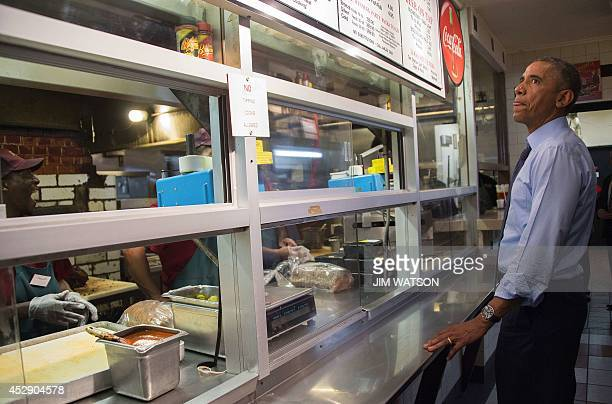 US President Barack Obama orders food at Arthur Bryant's Barbecue in Kansas City Missouri before having dinner with four local residents July 29 2014...