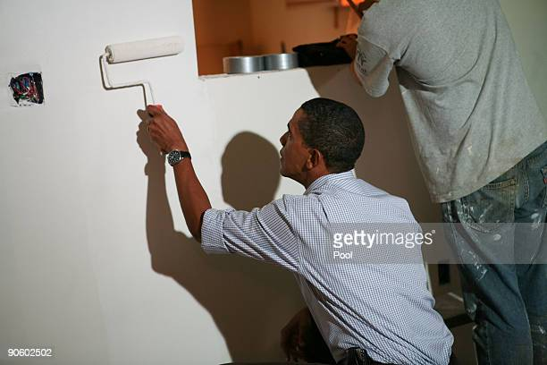US President Barack Obama paints in a house being built by Habitat for Humanity on September 11 2009 in Washington DC In observance of the eighth...