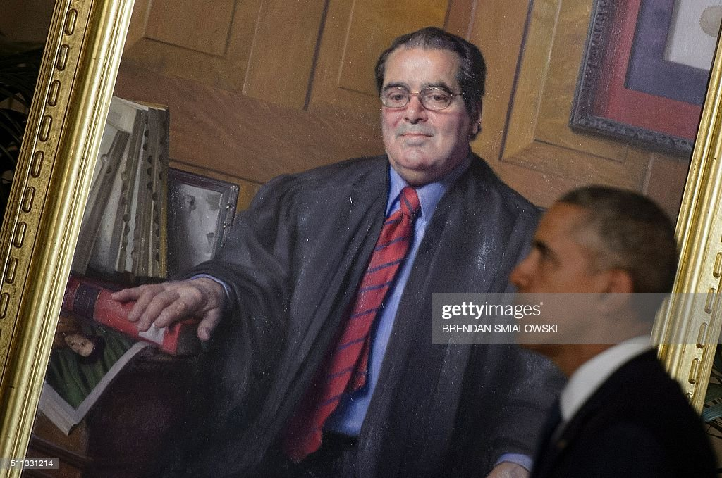 US President Barack Obama passes a portrait of Justice Antonin Scalia after paying respects as the Justices body lays in repose at the US Supreme Court February 19, 2016 in Washington, DC. / AFP / Brendan Smialowski