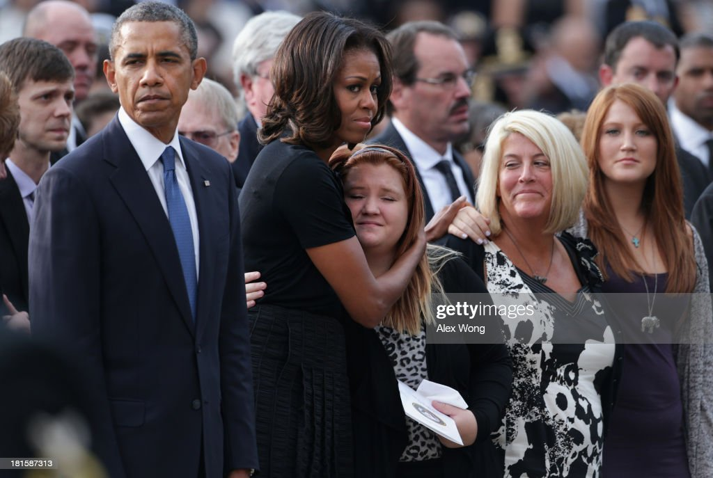 U.S. President <a gi-track='captionPersonalityLinkClicked' href=/galleries/search?phrase=Barack+Obama&family=editorial&specificpeople=203260 ng-click='$event.stopPropagation()'>Barack Obama</a> (L) pauses as first lady <a gi-track='captionPersonalityLinkClicked' href=/galleries/search?phrase=Michelle+Obama&family=editorial&specificpeople=2528864 ng-click='$event.stopPropagation()'>Michelle Obama</a> (2nd L) hugs a family membr during a memorial service for victims of the Washington Navy Yard shooting at the Marine Barracks September 22, 2013 in Washington, DC. The president and first lady <a gi-track='captionPersonalityLinkClicked' href=/galleries/search?phrase=Michelle+Obama&family=editorial&specificpeople=2528864 ng-click='$event.stopPropagation()'>Michelle Obama</a> visited with families of the victims in the deadly shooting at the Washington Navy Yard. Thirteen people, including the gunman Aaron Alexis, were killed in the incident.