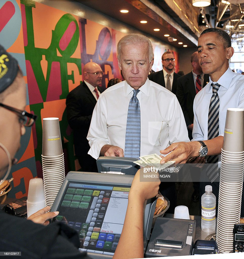 US President Barack Obama pays for lunch after he and Vice President Joe Biden (L) ordered lunch at Taylor Gourmet Deli on Pennsylvania Ave in Washington, DC on October 4, 2013. Obama walked over to the deli with US Vice President Joe Biden and ordered sandwiches to go. AFP PHOTO/Mandel NGAN