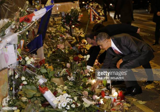 US President Barack Obama pays his respects with French President Francois Hollande at the memorial outside the Bataclan in Paris on November 30...