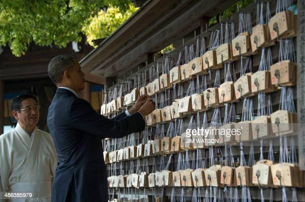 US President Barack Obama places a prayer tablet on the Votive Tree at the Meiji Shrine in Tokyo on April 24 2014 Obama earlier vowed to defend Japan...