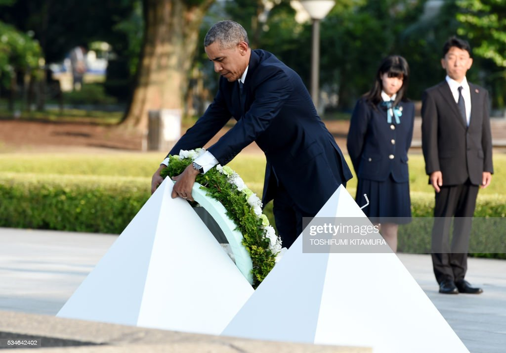 US President Barack Obama places a wreath at the cenotaph in the Peace Momorial park in Hiroshima on May 27, 2016 with Japanese Prime Minister Shinzo Abe. Obama on May 27 paid a moving tribute to victims of the world's first nuclear attack. / AFP / TOSHIFUMI