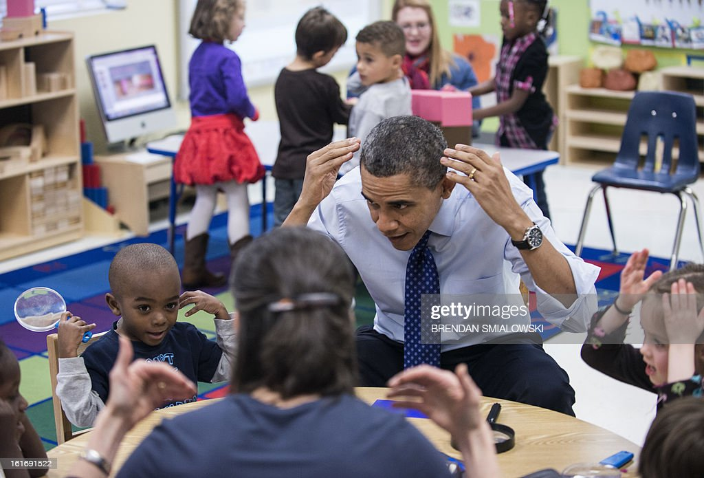 US President Barack Obama plays a learning game while visiting children at College Heights Early Childhood Learning Center February 14, 2013 in Decatur, Georgia. Obama is traveling to Georgia to promote economic and educational initiatives he spoke about in this week's State of the Union. AFP PHOTO/Brendan SMIALOWSKI