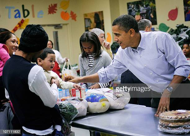 US President Barack Obama plays with the young child as he packs and gives bags of food to area residents with the help of his daughter Sasha center...