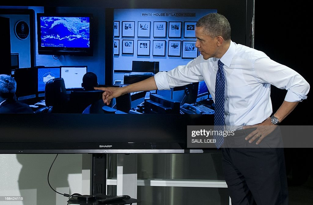 US President Barack Obama points to a picture of himself sitting in the White House Situation Room looking at a weather map created by Stormpulse during a visit to Capital Factory, a tech start-up incubator and co-working space in Austin, Texas, May 9, 2013. AFP PHOTO / Saul LOEB