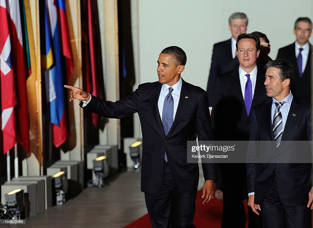 U.S. President Barack Obama (L) points to Lake Michigan as he leads NATO Secretary General Anders Fogh Rasmussen and the rest of the world leaders as they walk under the Soldier Field colonnades to the family photo during the NATO Summit on May 20, 2012 in Chicago, Illinois. As sixty heads of state converge for the two day summit that will address the situation in Afghanistan, among other global defense issues, thousands of demonstrators have taken to the streets to protest.