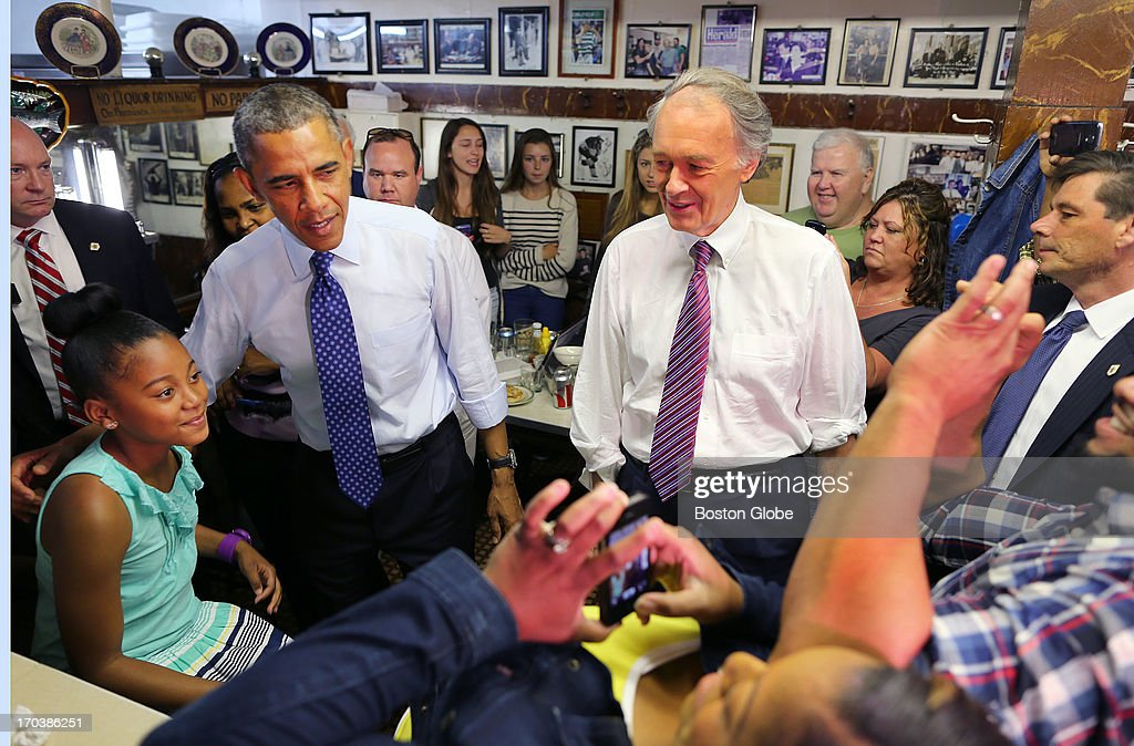 President Barack Obama poses for a photo with Leilani Guthrie, 11, from Boston as her parents, Natalie and Sean, take a photo, as Congressman Ed Markey looks on at Charlie's Sandwich Shoppe in the South End. President Barack Obama visited Boston on behalf of Congressman Ed Markey, who is running for the open U.S. Senate seat vacated by Secretary of State John Kerry. Previously, the President attended a rally at the Reggie Lewis Track and Athletic Center.