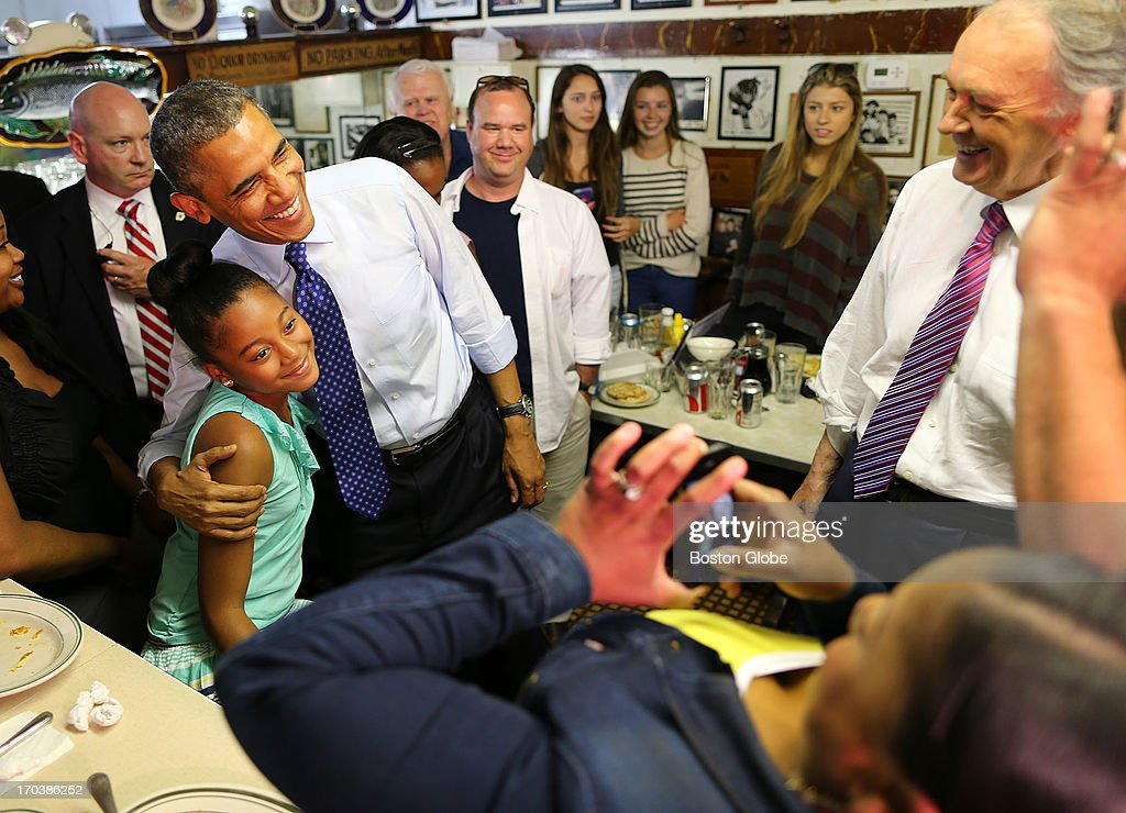 President Barack Obama poses for a photo with Leilani Guthrie, 11, from Boston, as her parents, Natalie and Sean take a photo, as Congressman Ed Markey looks on at Charlie's Sandwich Shoppe in the South End. President Barack Obama visited Boston on behalf of Congressman Ed Markey, who is running for the open U.S. Senate seat vacated by Secretary of State John Kerry. Previously, the President attended a rally at the Reggie Lewis Track and Athletic Center.