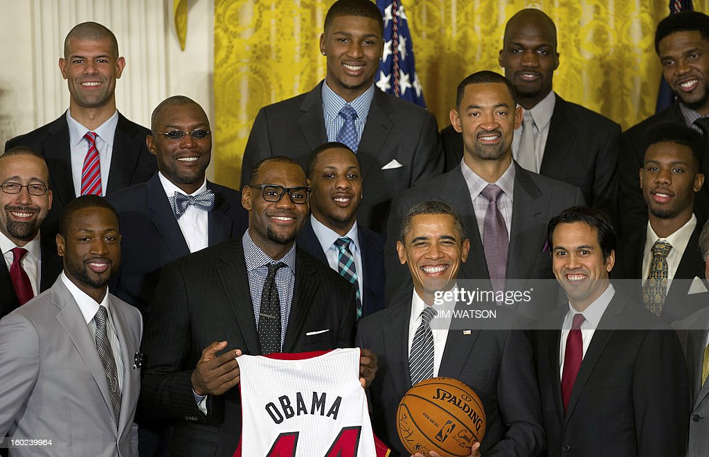 US President Barack Obama (C) poses with Dwyane Wade (Front-L), LeBron James (2nd-L-holding jersey) and Coach Erik Spoelstra (Front-R) as he welcomes the NBA Champion Miami Heat to the White House to honor the team and their 2012 NBA Championship victory at the White House in Washington, DC, January 28, 2013. AFP PHOTO/Jim WATSON