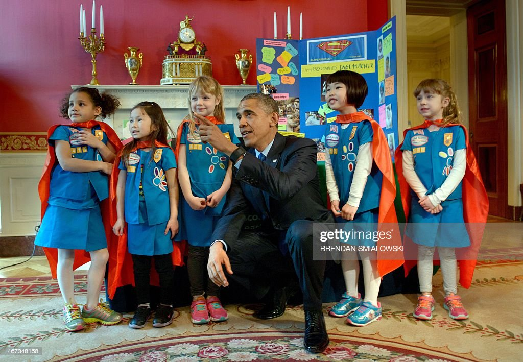 US President Barack Obama poses with girl scouts from Tulsa, Oklahoma during the 2015 White House Science Fair March 23, 2015 in Washington, DC. The fair celebrates student winners who created projects to illustrate mastery of science, technology, math or engineering.