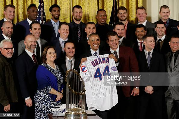 US President Barack Obama poses with presented jersey as he welcomes the World Champion Chicago Cubs baseball team to the White House in Washingto DC...