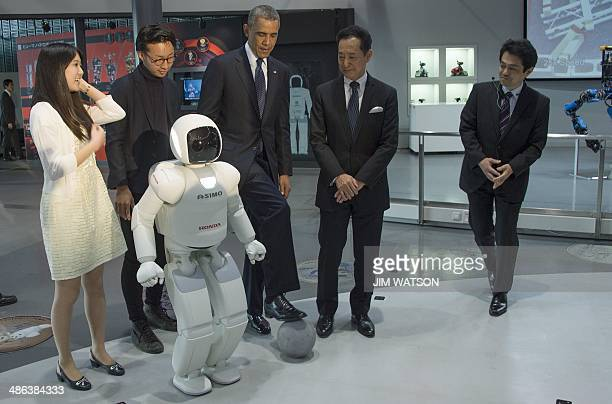 US President Barack Obama positions a football as he talks with Honda's humanoid robot ASIMO an acronym for Advanced Step in Innovative MObility...