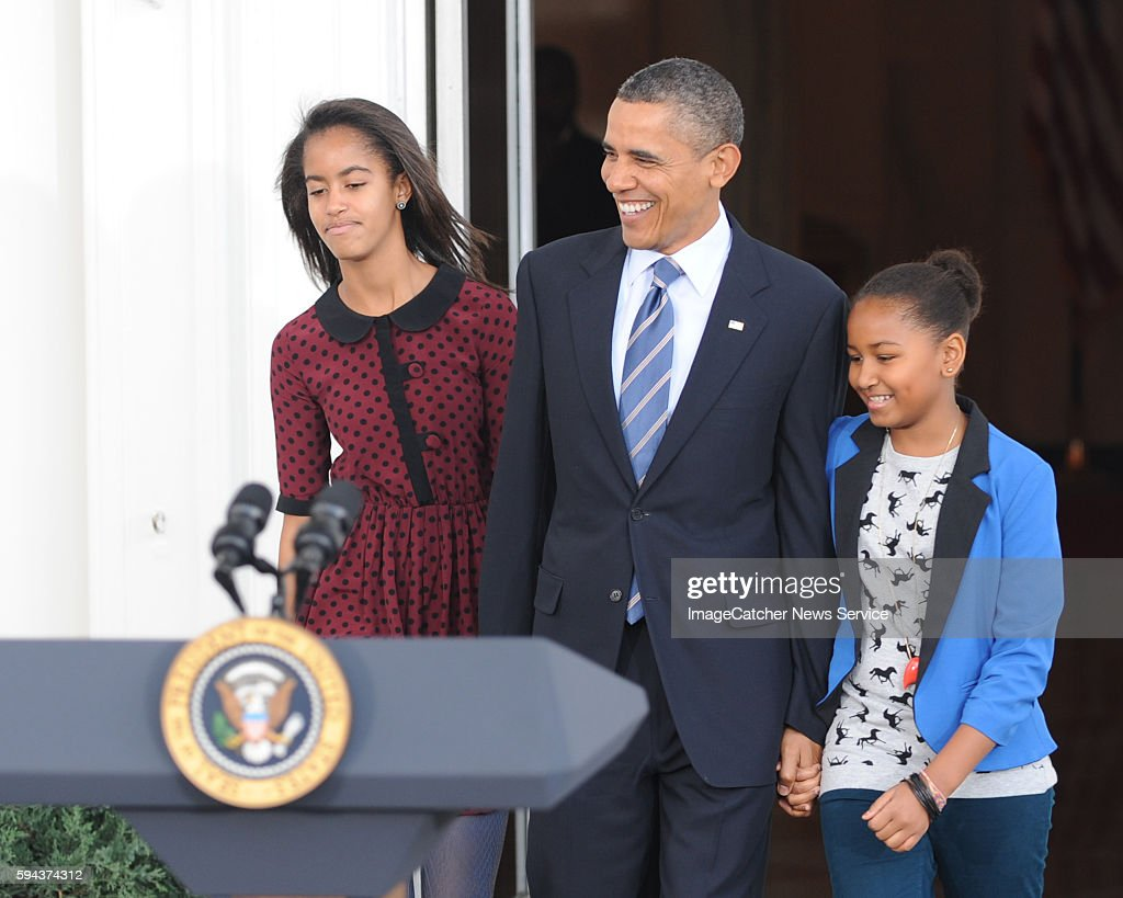 President Barack Obama prepares to pardon this year's Thanksgiving Turkey named Liberty at the North Portico of the White House as daughters Maila...