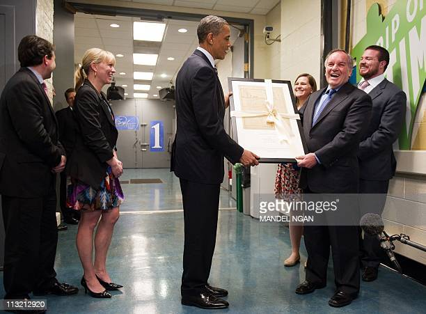 US President Barack Obama presents a gift to outgoing Chicago Mayor Richard Daley following a taping of the Oprah Winfrey show April 27 2011 at Harpo...