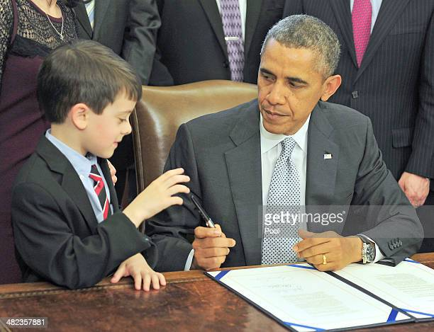 S President Barack Obama presents a pen to Jacob Miller brother of Gabriella Miller after signing HR 2019 the Gabriella Miller Kids First Research...