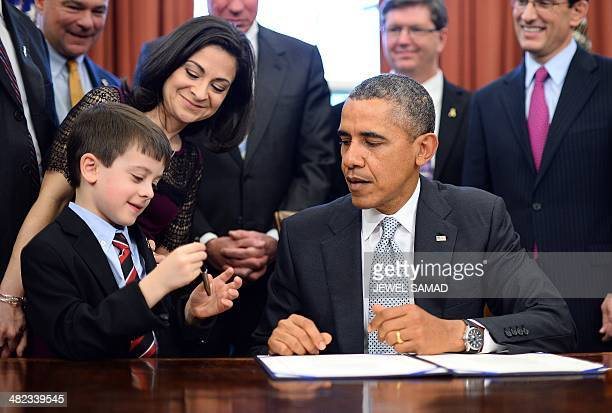 US President Barack Obama presents a pen to Jake Miller after he signed HR 2019 the Gabriella Miller Kids First Research Act into law in the Oval...