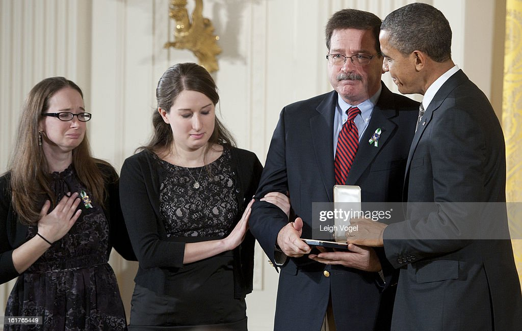 President Barack Obama presents Bill Sherlach and daughters Katy Sherlach and Maura Lynn Schwartz with the 2012 Presidential Citizens Medal, the nation's second-highest civilian honor, on behalf of their wife and mother Mary Sherlach at the White House on February 15, 2013 in Washington, DC.