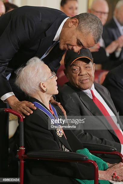 S President Barack Obama presents pioneering NASA mathematician Katherine Johnson with the Presidential Medal of Freedom as Willie Mays look on...